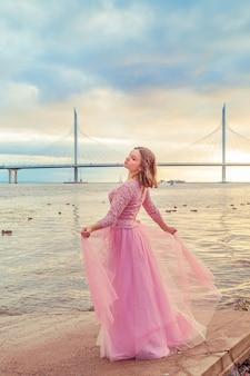 Młoda dziewczyna w różowej sukience tańczy nad brzegiem morza. beztroska, wolność, młodość. letni wieczór.
