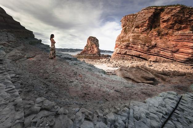 Młoda dziewczyna w skalistym krajobrazie na wybrzeżu.
