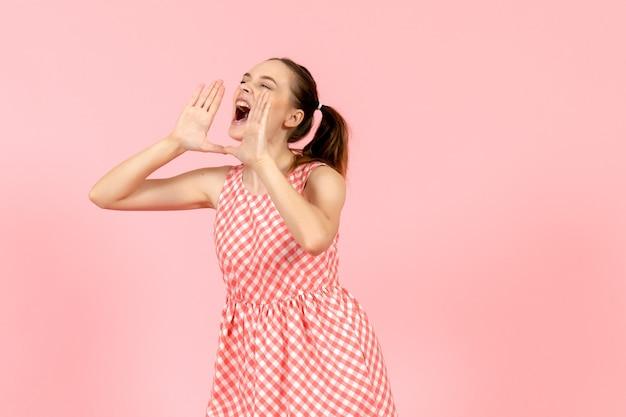 Młoda dziewczyna w ślicznej jasnej sukience głośno wzywając kogoś na różowo