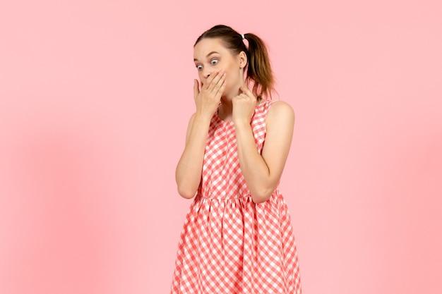 Młoda dziewczyna w ślicznej jasnej sukni z zszokowanym wyrazem na różowo