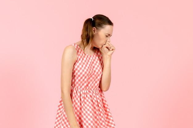Młoda dziewczyna w ślicznej różowej sukience kaszle na różowo
