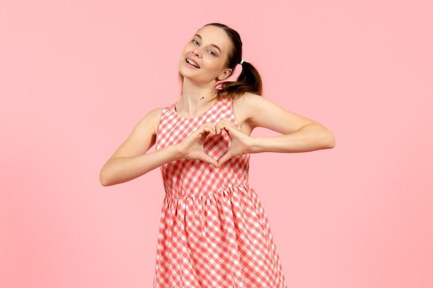 Młoda dziewczyna w ślicznej różowej sukience wysyłając miłość na różowo