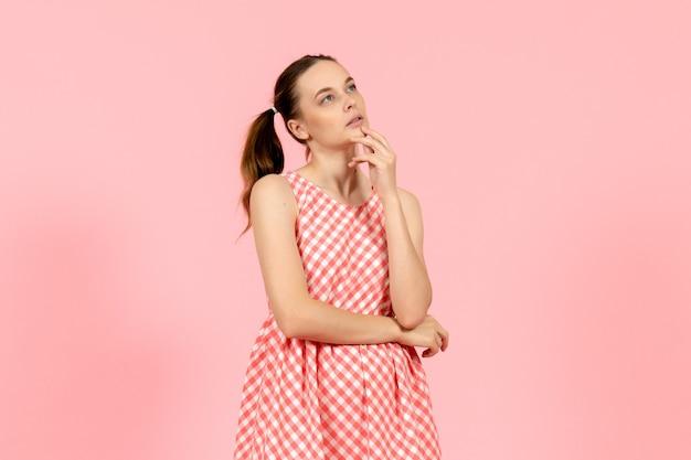 Młoda dziewczyna w ślicznej różowej sukience z wyrażeniem myślenia na różowo