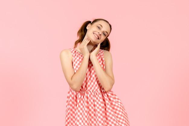 Młoda dziewczyna w ślicznej różowej sukience z zachwyconą twarzą na różowo