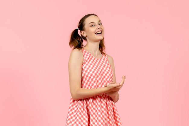 Młoda dziewczyna w ślicznej różowej sukience z zachwyconym wyrazem na różowo