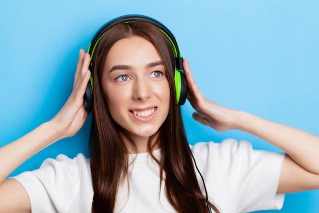 Młoda dziewczyna w słuchawkach słucha muzyki