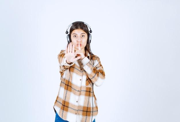 Młoda dziewczyna w słuchawkach stojąc na białej ścianie.