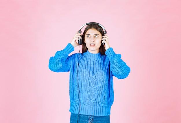 Młoda dziewczyna w słuchawkach stojąc na nk.