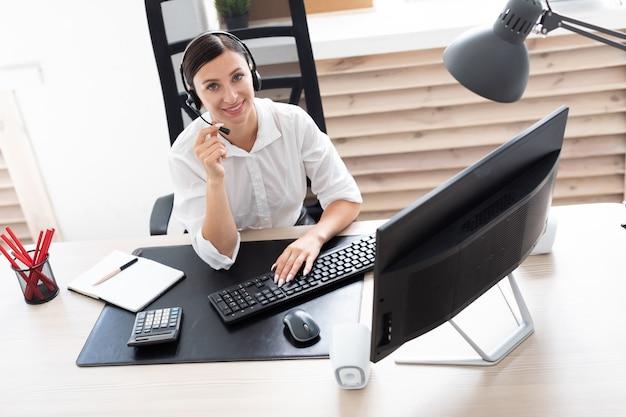 Młoda dziewczyna w słuchawkach z mikrofonem siedzi przy stole komputera.