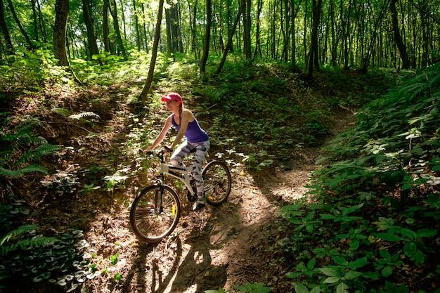 Młoda dziewczyna w sport odzieży z rowerową jazdą w lesie w lecie