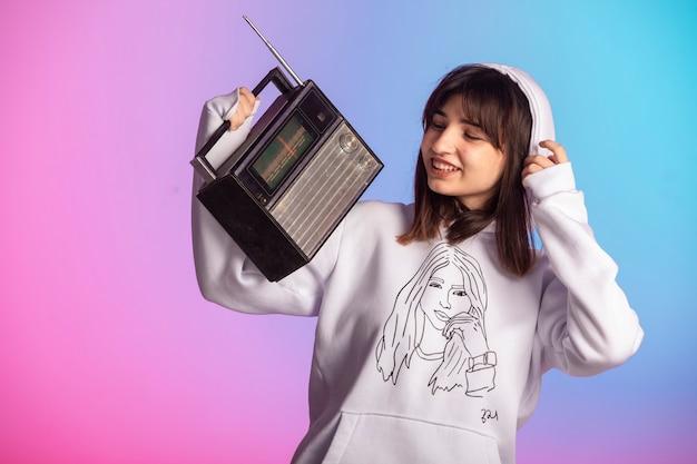 Młoda dziewczyna w strojach sportowych, trzymając vintage radio i zabawy.