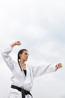 Młoda dziewczyna w stroju sztuki walki na zewnątrz