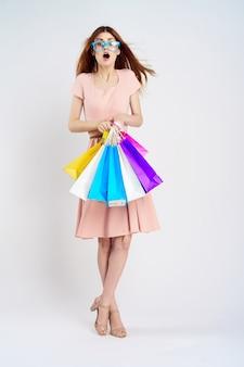 Młoda dziewczyna w sukience z torby na zakupy w ręce na lekkiej ścianie, zakupoholiczka