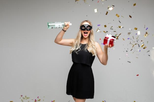 Młoda dziewczyna w świątecznej masce z prezentem i butelką wina świętuje wakacje na szarym tle z konfetti, kopia przestrzeń