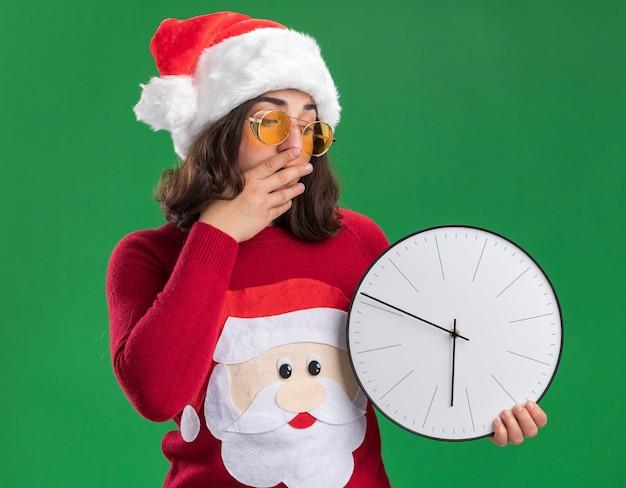 Młoda dziewczyna w świątecznym swetrze w czapce świętego mikołaja i okularach trzyma zegar ścienny patrząc na niego zdziwiona i zaskoczona zakrywająca usta ręką stojącą na zielonym tle