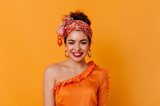 Młoda dziewczyna w świetnym nastroju uśmiecha się na pomarańczowej przestrzeni. stylowa ciemnowłosa dama w pomarańczowej bluzce i szaliku na głowie patrzy w kamerę.
