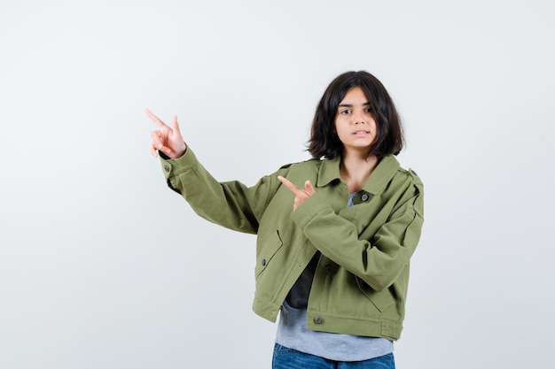 Młoda dziewczyna w szarym swetrze, kurtce khaki, spodniach dżinsowych wskazujących w lewo palcami wskazującymi i patrząca poważnie, widok z przodu.