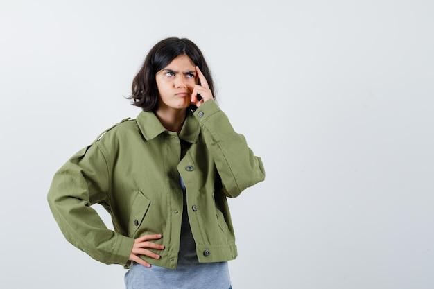 Młoda dziewczyna w szarym swetrze, kurtka khaki, spodnie dżinsowe, trzymając rękę w pasie, jednocześnie drapiąc się po głowie i patrząc zamyślony, widok z przodu.