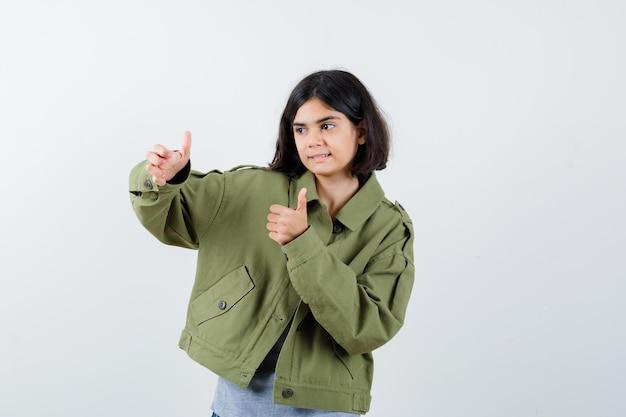 Młoda dziewczyna w szarym swetrze, kurtka khaki, spodnie jeansowe pokazujące kciuki obiema rękami i patrząc poważnie, widok z przodu.