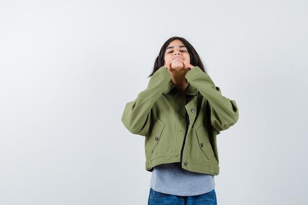 Młoda dziewczyna w szarym swetrze, kurtka khaki, spodnie jeansowe trzymające palce wskazujące w pobliżu ust, zmuszając się do uśmiechu i patrząc ładnie, widok z przodu.