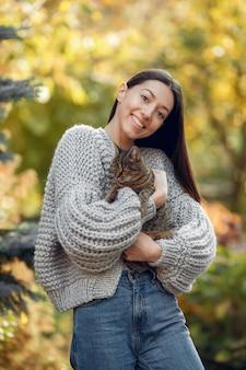 Młoda dziewczyna w szarym swetrze pozuje outdoors z kotem