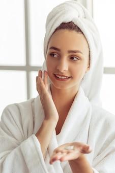 Młoda dziewczyna w szlafroku i ręcznikiem na głowie.