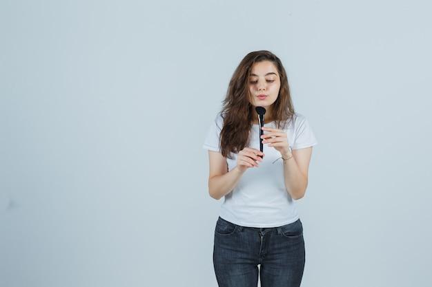 Młoda dziewczyna w t-shirt, dżinsy dmuchanie proszku na pędzel do makijażu i patrząc skoncentrowany, widok z przodu.