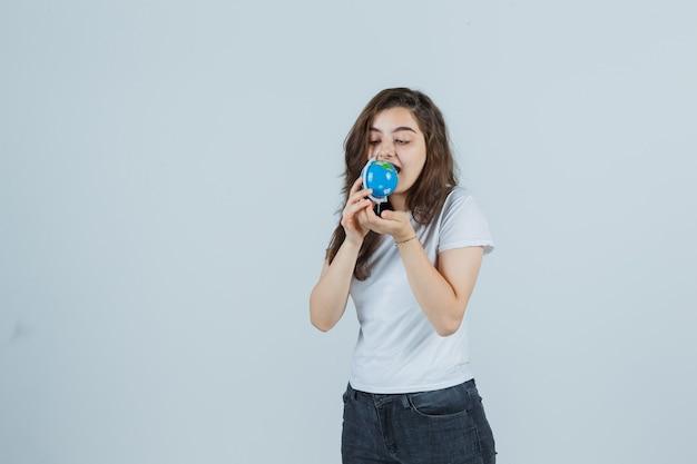 Młoda dziewczyna w t-shirt, dżinsy, próbuje ugryźć kulę ziemską i wygląda szalenie, widok z przodu.