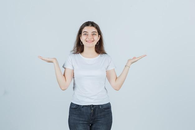 Młoda dziewczyna w t-shirt, dżinsy, rozkładające dłonie i wyglądające na szczęśliwego, widok z przodu.