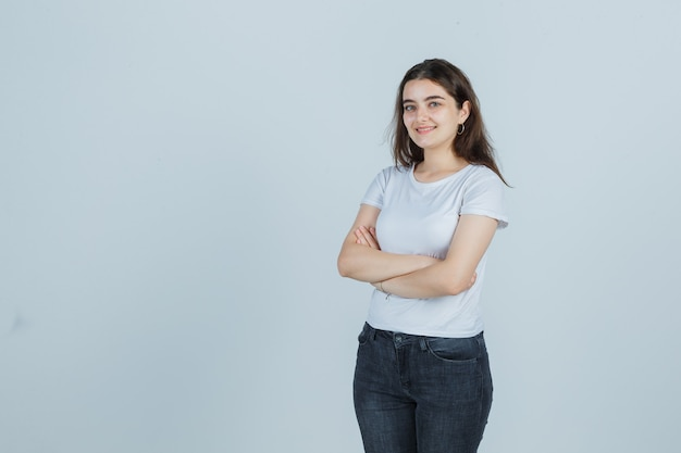 Młoda dziewczyna w t-shirt, dżinsy, stojąc ze skrzyżowanymi rękami i patrząc radośnie, widok z przodu.