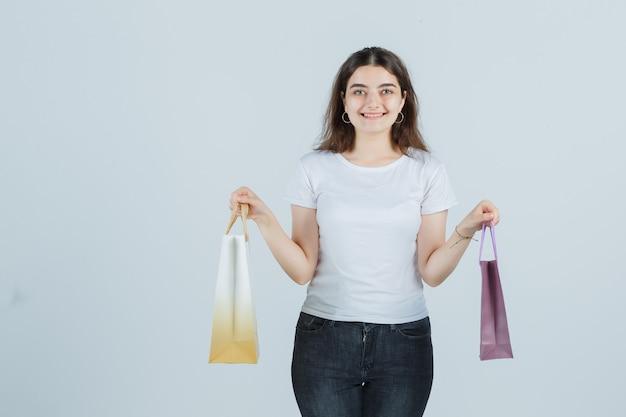 Młoda dziewczyna w t-shirt, dżinsy, trzymając torby na prezenty i patrząc szczęśliwy, widok z przodu.