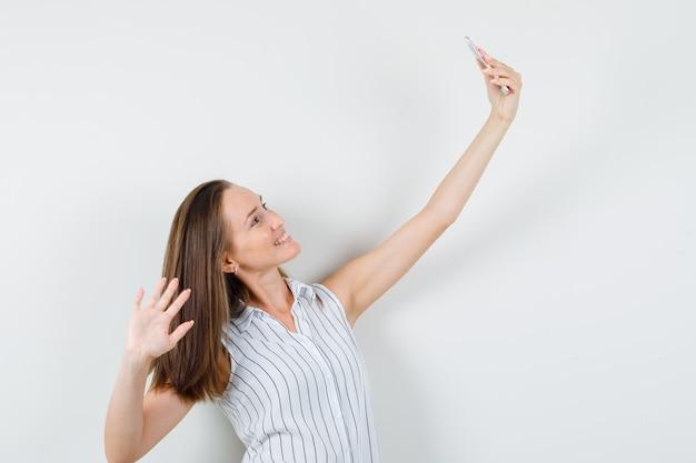 Młoda dziewczyna w t-shirt pozowanie podczas robienia selfie i patrząc szczęśliwy, widok z przodu.