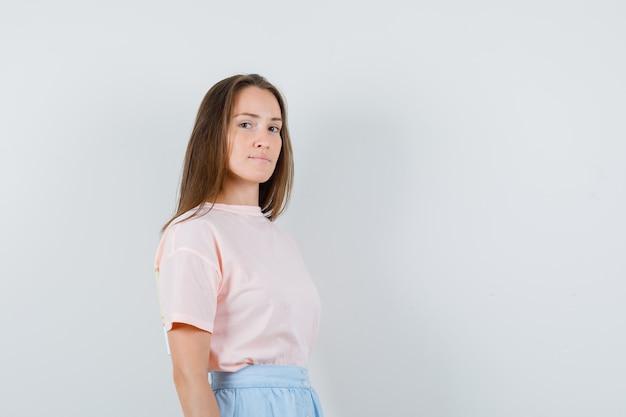 Młoda dziewczyna w t-shirt, spódnica patrząc na kamery i patrząc pewnie, z przodu.