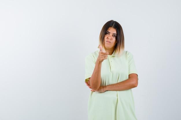 Młoda dziewczyna w t-shirt, wskazując na aparat z palcem wskazującym i patrząc poważny, przedni widok.
