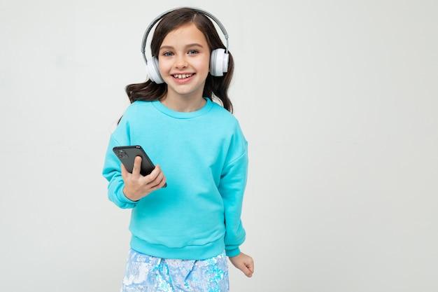Młoda dziewczyna w turkusowej bluzce trzyma telefon na studiu z kopii przestrzenią słucha muzyka z hełmofonami