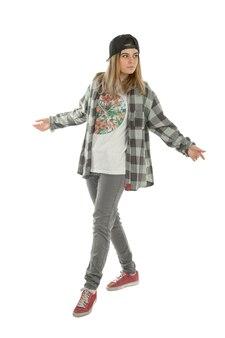 Młoda dziewczyna w ubrania w stylu hip-hop na białym tle na białej ścianie w studio
