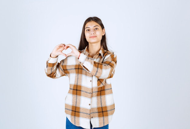 Młoda dziewczyna w ubranie stojące i pozowanie na białej ścianie.