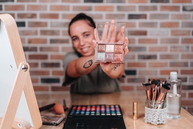Młoda dziewczyna w wieku 20 lat pokazująca paletę makijażu do kamery