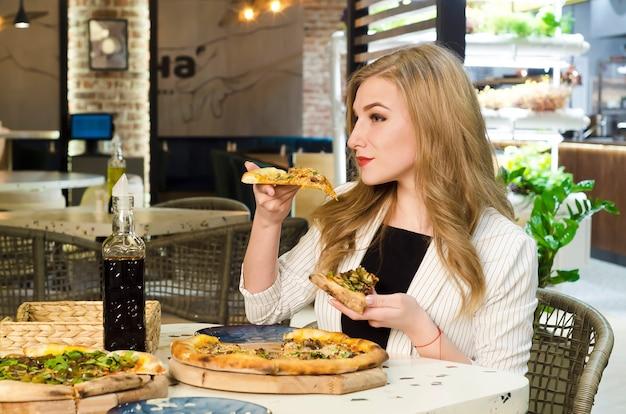 Młoda dziewczyna w włoskiej restauracji, jedząc plastry pizzy rękami