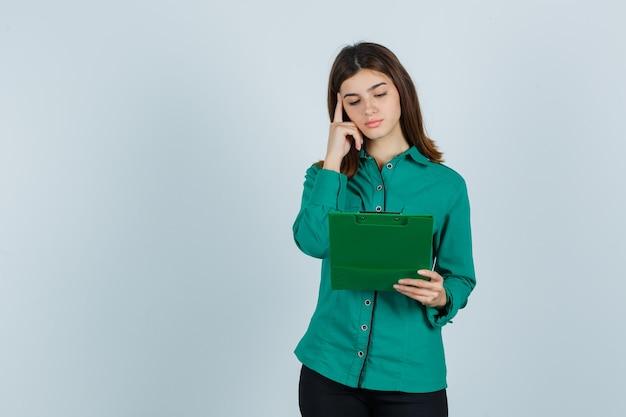 Młoda dziewczyna w zielonej bluzce, czarnych spodniach patrząc na schowek, kładąc palec wskazujący na skroni i patrząc zamyślony, widok z przodu.