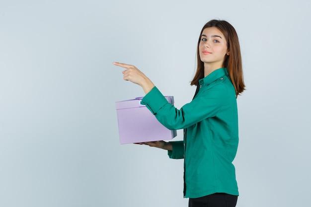 Młoda dziewczyna w zielonej bluzce, czarnych spodniach trzyma pudełko, wskazując w lewo i patrząc wesoło, widok z przodu.