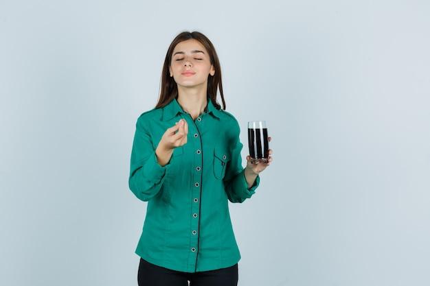 Młoda dziewczyna w zielonej bluzce, czarnych spodniach trzyma szklankę czarnego płynu, pokazuje włoski gest i wygląda na zadowoloną, widok z przodu.