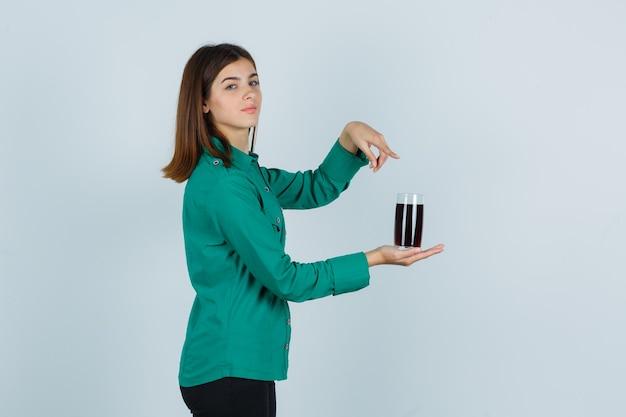 Młoda dziewczyna w zielonej bluzce, czarnych spodniach trzyma szklankę czarnego płynu, wskazując palcem wskazującym i patrząc wesoło, widok z przodu.