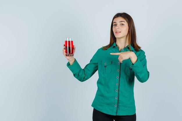 Młoda dziewczyna w zielonej bluzce, czarnych spodniach trzyma szklankę czerwonego płynu, wskazując na to i wyglądając uroczo, widok z przodu.