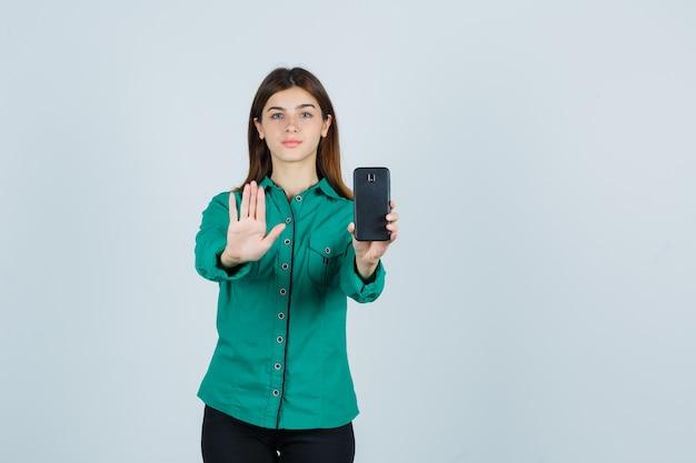 Młoda dziewczyna w zielonej bluzce, czarnych spodniach trzyma telefon w jednej ręce, pokazuje znak stopu i wygląda poważnie, widok z przodu.