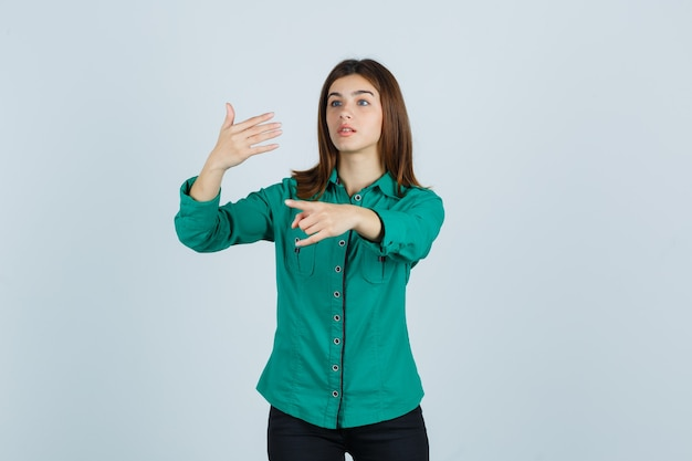 Młoda dziewczyna w zielonej bluzce, czarnych spodniach, wyciągając rękę, trzymając coś wyimaginowanego, pokazując gest rock and rolla i patrząc skupiony na przód.