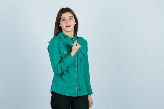 Młoda dziewczyna w zielonej bluzce, czarnych spodniach zaciskająca pięść na piersi i wyglądająca wesoło, widok z przodu.