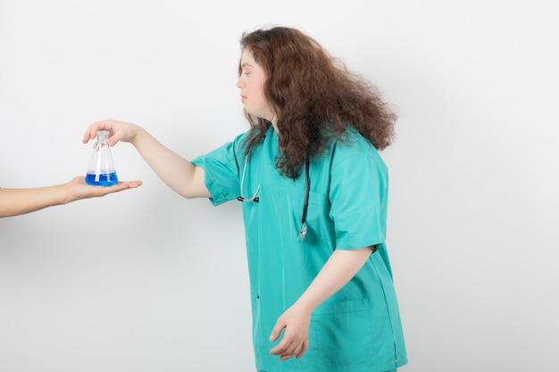 Młoda dziewczyna w zielonym mundurze trzyma szklany słoik z niebieskim płynem.