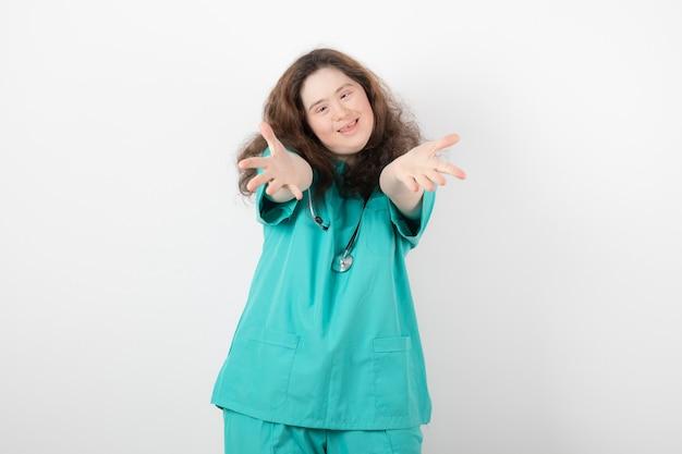 Młoda dziewczyna w zielonym mundurze ze stetoskopem stojąc i pozowanie.