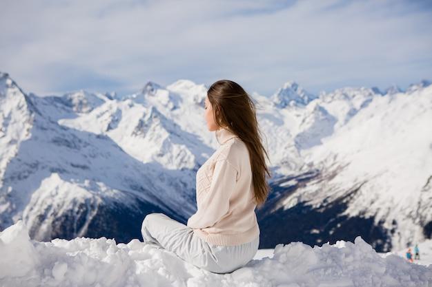 Młoda dziewczyna w zimowym garniturze, patrząc na góry